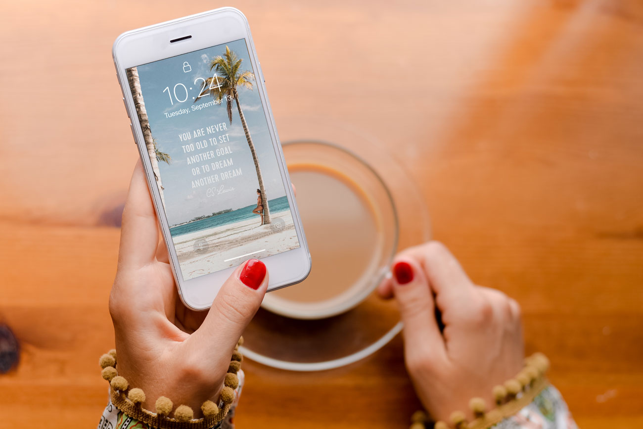 person holding phone with inspirational wallpaper