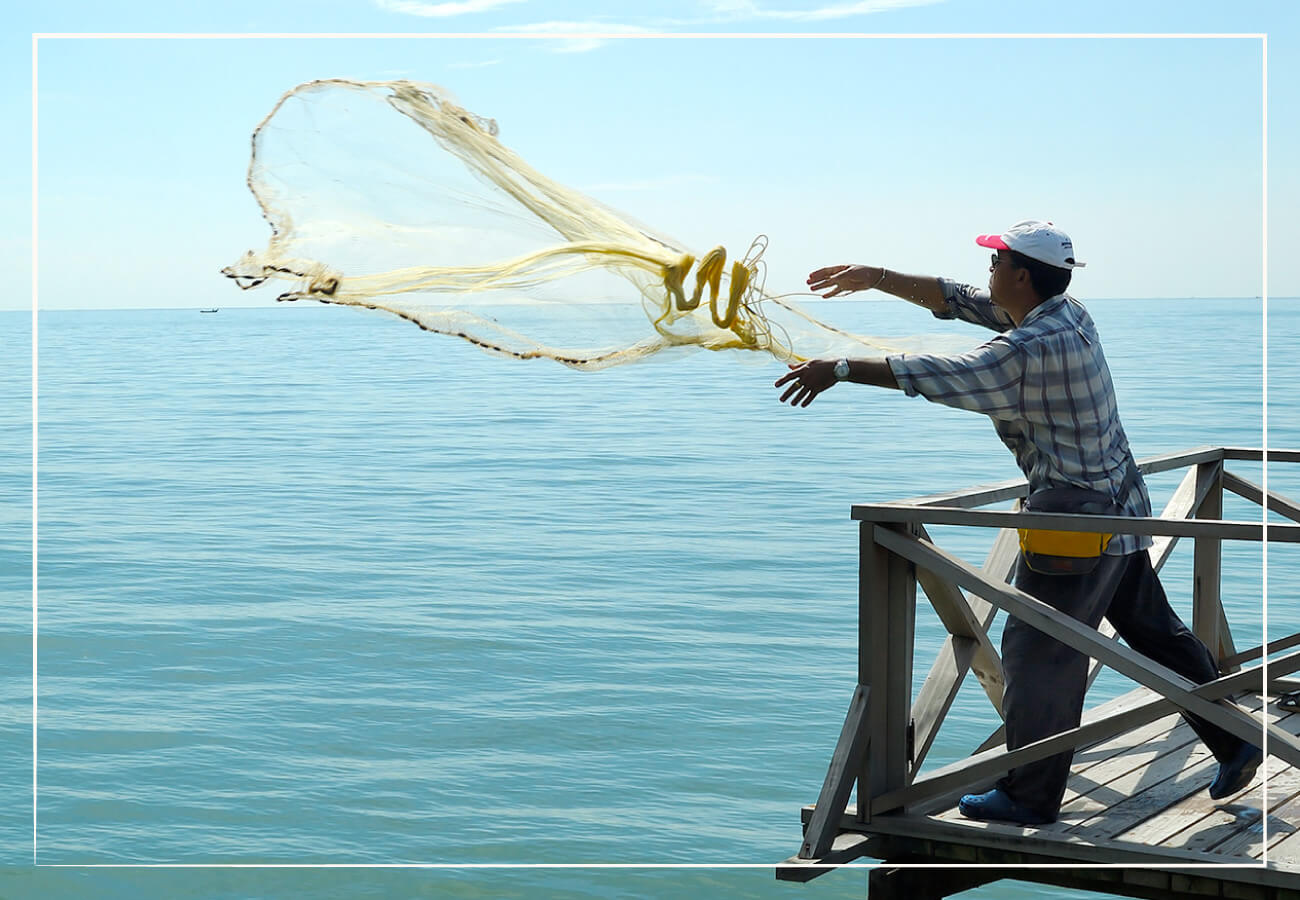 person throwing net into the ocean
